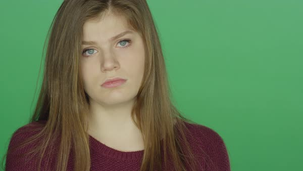 Young brunette woman looking sad, on a green studio background Royalty-free stock video