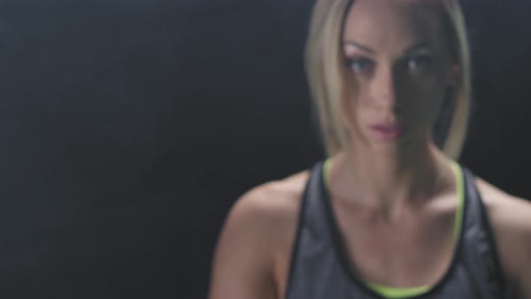 Focusing shot of an athletic woman staring at the camera on a foggy dark background Royalty-free stock video