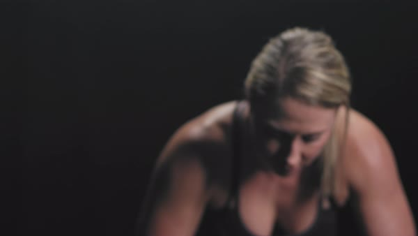 Focusing shot of an athletic woman resting in between workouts on a dark background Royalty-free stock video