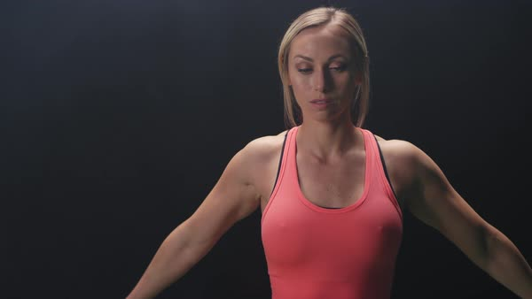 Athletic woman stretching her arms on a foggy dark background Royalty-free stock video