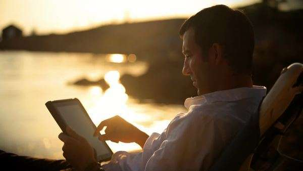 A young man sitting down outside during magic hour looking at a tablet Royalty-free stock video
