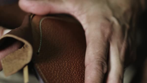 Close-up shot of a craftsman holding a piece of leather Royalty-free stock video