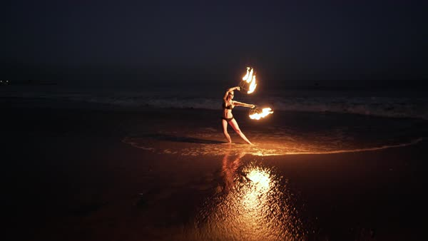 Drone shot of a fire dancer performing with fire fans on a beach Royalty-free stock video