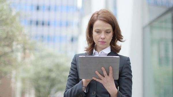 Business woman types into her digital tablet, medium shot Royalty-free stock video