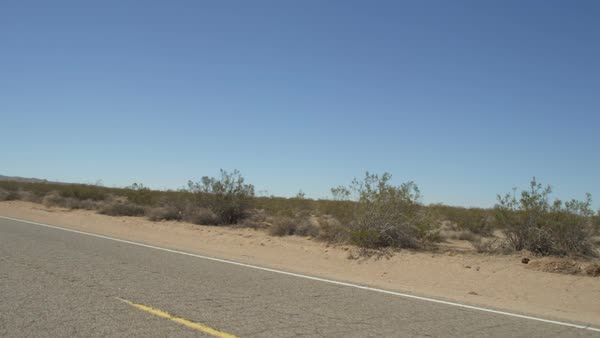 Left Rear Three Quarter view of a Driving Plate: Car travels east on Shadow  Mountain Road through the Southern California desert  stock footage