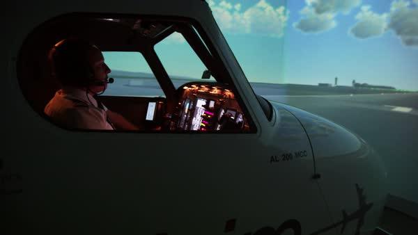 Medium shot of pilots and instructor in professional flight simulator,  Malaga, Andalusia, Spain stock footage