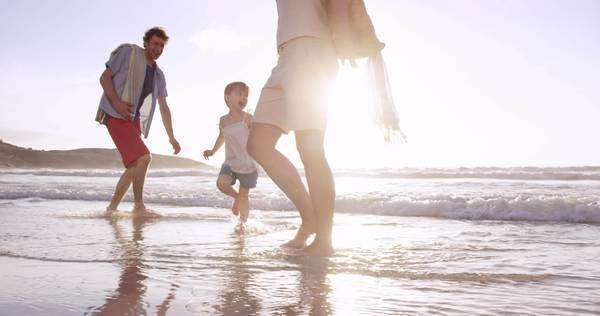 Happy family playing in the waves on the beach at sunset on vacation slow motion Royalty-free stock video