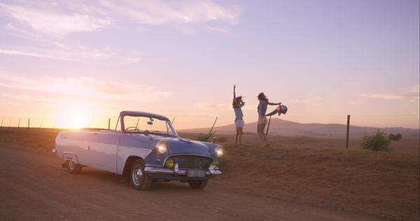 Girl friends dancing at sunset on road trip with vintage car Royalty-free stock video