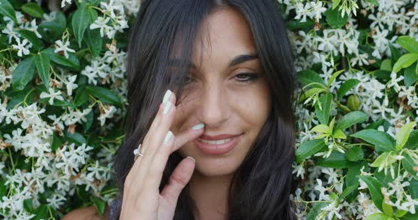 Close-up portrait of beautiful young woman running hand through hair smiling in front of wall of flowers slow motion Royalty-free stock video