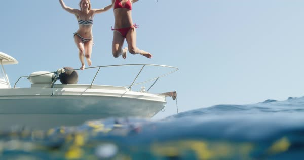 Young women jumping off boat into ocean Royalty-free stock video