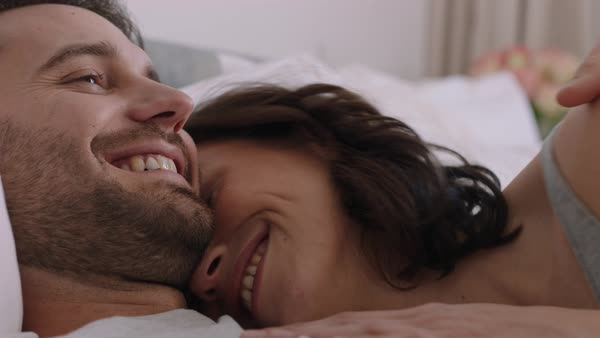 Happy young couple lying in bed embracing sharing romantic relationship  enjoying intimacy together at home stock footage