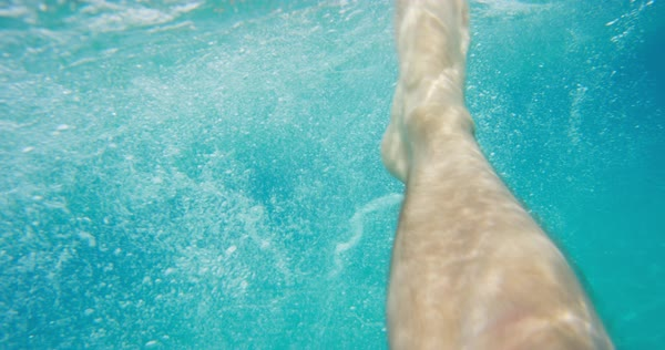 Feet floating in ocean waves from underwater  light rays shining through from beneath surface clear blue water nature background Royalty-free stock video