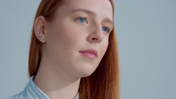 Studio shoot with ginger hair model with big blue eyes, tucking hair behind  ear stock footage