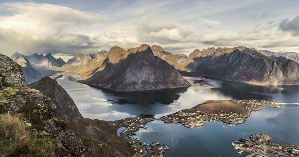 High-angle view timelapse of an island mountain range surrounded by water with dramatic cast shadows. Reinebringen, Lofoten Islands, Norway Royalty-free stock video