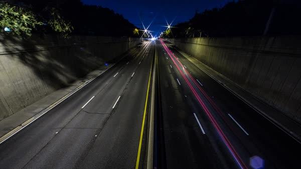 Traffic on urban highway at sunrise stock footage