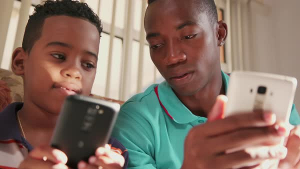 Father teaching son how to use mobile phone Royalty-free stock video
