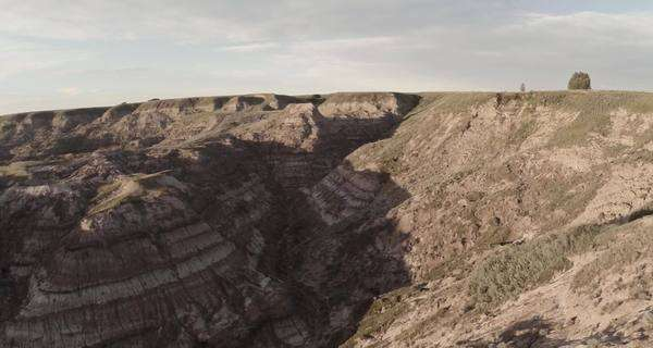 Aerial extreme wide shot of sunlit badlands in Drumheller, Alberta Royalty-free stock video