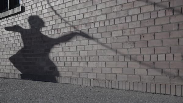 Wide-angle shot of shadow of a hula hoop dancer on a brick wall Royalty-free stock video