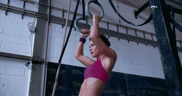 Fit girl looking focused and determined while doing pull-ups in a gym on gymnastic rings Royalty-free stock video