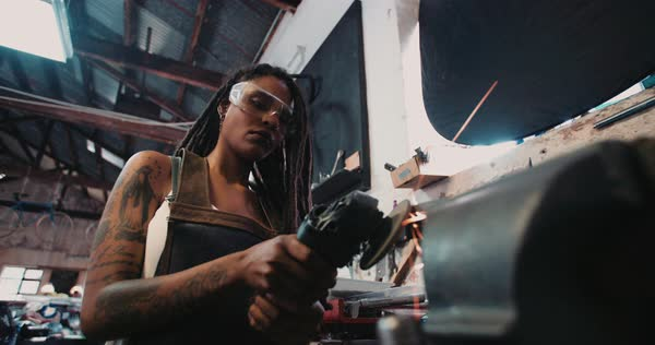 Low angle shot of a skilled woman craftsperson with dreadlocks and tattoos using a grinder on a piece of metal with sparks Royalty-free stock video