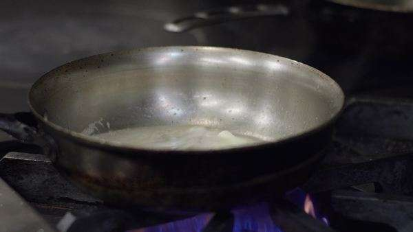 Close-up shot of a chef adding pasta into a pan Royalty-free stock video
