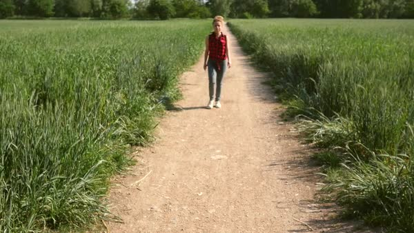 Wide shot of a woman walking on a grassy path in Verona, Italy in slow motion Royalty-free stock video