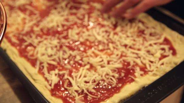 Hand-held shot of cheese being put on home made pizza. Royalty-free stock video