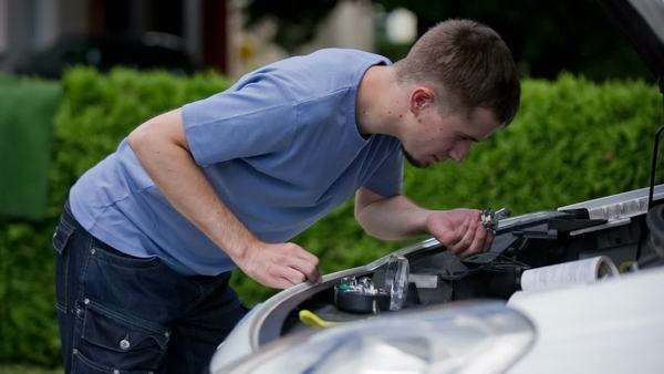 Man put out bulb from car headlight and look at it  Young