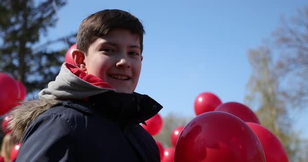 Hand-held shot of a boy standing among red balloons Royalty-free stock video
