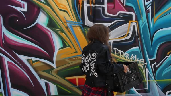 Medium shot of woman in leather jacket carrying crate of aerosol cans Royalty-free stock video