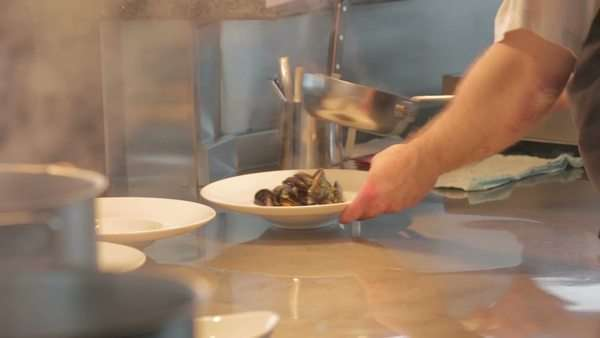 Chef preparing mussels in kitchen to be plated up Royalty-free stock video