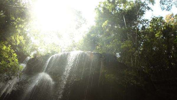 Spin downward with lens flare toward large waterfall Royalty-free stock video