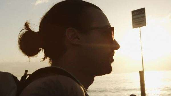 Man with ponytail looks out at ocean with lens flare Royalty-free stock video