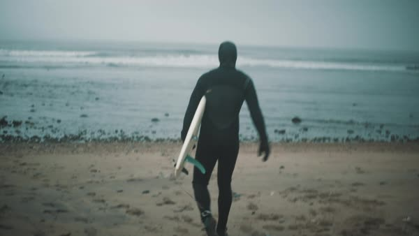 Surfer with board walks toward ocean Royalty-free stock video