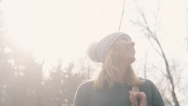 Girl smiles and turns with lens flare behind her Royalty-free stock video