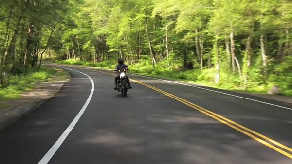 Motorcycle driving on back road through woods Royalty-free stock video