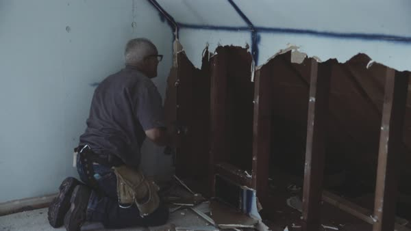 Hand-held shot of a man tearing down drywall Royalty-free stock video