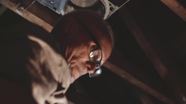 Low-angle shot of a man fixing a lamp in an attic Royalty-free stock video