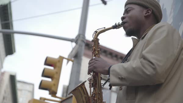Hand-held shot of a man playing a saxophone on a street Royalty-free stock video