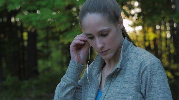 Handheld shot of a woman listening to music while jogging Royalty-free stock video
