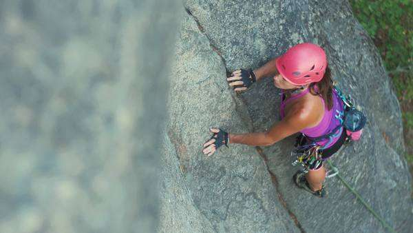 Medium shot of a woman climbing up a cliff Royalty-free stock video