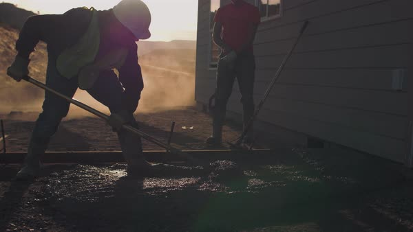 Two construction workers spreading newly poured concrete Royalty-free stock video