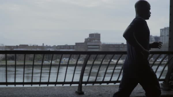 Medium shot of a man running on a riverside Royalty-free stock video