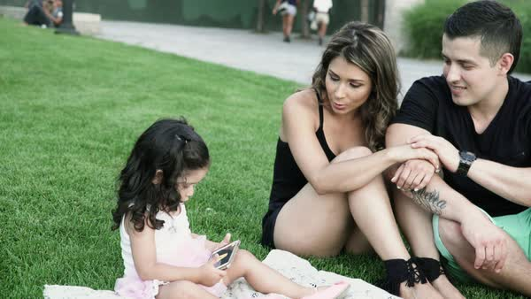 Medium shot of young parents and little girl sitting on grass using cell phone Royalty-free stock video