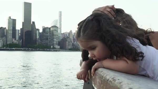 Hand-held shot of a little girl and her mother along a riverside Royalty-free stock video