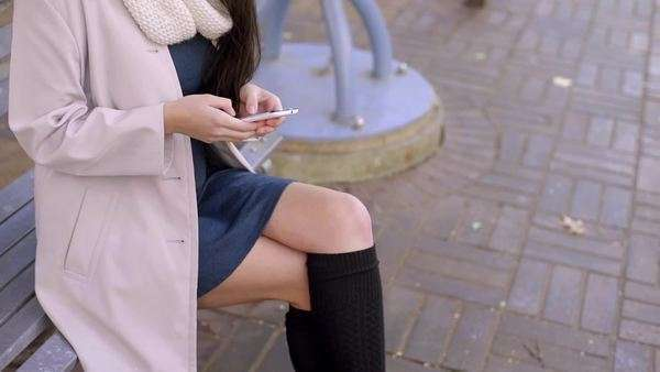Young woman sits on bench and texts on her smartphone Royalty-free stock video
