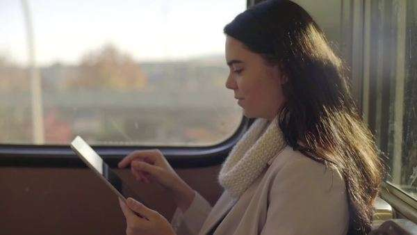 Close up of happy young woman using her tablet on a train Royalty-free stock video