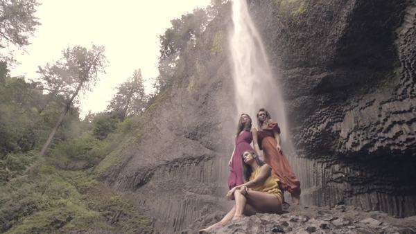 Young women pose beneath epic waterfall in wind and mist, slow motion Royalty-free stock video