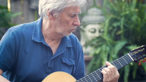 Healthy active fit baby boomer man concentrating on playing acoustic guitar  outdoors in his garden in the summer stock footage