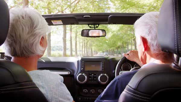 Rear passenger POV of senior couple driving an open top car stock footage